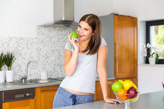Happy young woman eating green apple. In modern kitchen Royalty Free Stock Photography