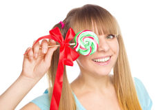 Happy young woman is eating her colorful lollipop Royalty Free Stock Photo