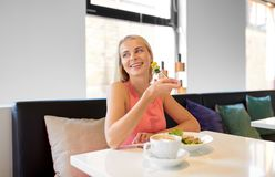 Happy young woman eating lunch at restaurant royalty free stock photo