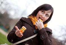 Happy young woman eating macaroons Royalty Free Stock Photography