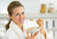 Happy young woman eating muesli in kitchen Stock Photo