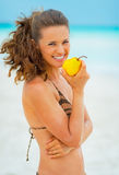 Happy young woman eating pear on beach Stock Images