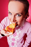 Happy young woman eating piece of pizza Stock Images
