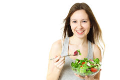 Happy young woman eating salad. Royalty Free Stock Images