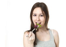 Happy young woman eating salad. Stock Photography
