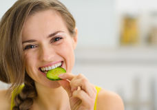 Happy young woman eating slice of cucumber Stock Image