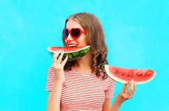 Happy young woman is eating slice of watermelon. Over a colorful blue background stock images