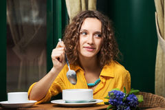 Happy young woman eating soup at restaurant Stock Images