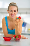 Happy young woman eating strawberry with yogurt. In kitchen Royalty Free Stock Photography