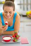 Happy young woman eating strawberry with yogurt. In kitchen Stock Images