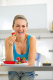 Happy young woman eating strawberry with yogurt. In kitchen Royalty Free Stock Photos