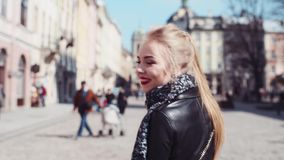 Happy young woman in an elegant wear walking in Lviv's center, turns to camera and smiles. Being happy, sunny day stock footage