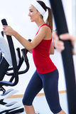 Happy young woman  with elliptic machine in the gym Stock Image