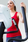 Happy young woman  with elliptic machine in the gym. Portrait of young woman with elliptic machine in the gym Stock Photos