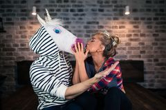 Happy young woman embraces with funny man in comical mask. Happy young women embraces with funny men in comical mask and sits on the bed in stylish apartment Royalty Free Stock Photography