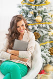 Happy young woman embracing tablet pc near christmas tree Stock Images