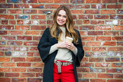 Happy young woman enjoy drinking coffee outdoors near red brick wall wearing warm autumn clothes Royalty Free Stock Images
