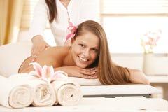 Happy young woman enjoying back massage royalty free stock photos