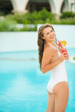 Happy young woman enjoying cocktail at poolside Royalty Free Stock Image