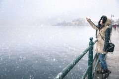 Woman reaching snowflakes on a snowy day. Happy young woman enjoying the first snowfall, reaching to catch snowflakes, on the Hallstatter See lakeshore, in the Royalty Free Stock Photography