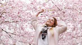 Happy young woman enjoying fresh air at spring blossom park Stock Images