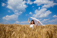 Happy young woman enjoying life in golden wheat field Stock Images