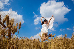 Happy young woman enjoying life in golden wheat field Royalty Free Stock Photos