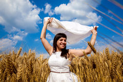 Happy young woman enjoying life in golden wheat field Royalty Free Stock Images