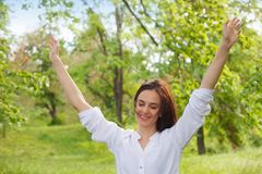 Happy young woman enjoying nature in a park. Beautiful Girlin white with arms up. Outdoor image royalty free stock photography