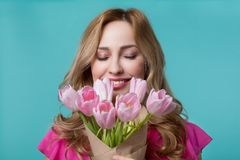 Happy young woman enjoying scent of tulips. Wonderful present. Portrait of excited girl smelling flowers and smiling. Her eyes are closed with enjoyment stock photos