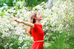 Happy young woman enjoying smell in flowering spring garden Royalty Free Stock Image