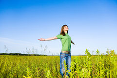 Happy young woman enjoying summer. Against the backdrop of blue sky Stock Photos