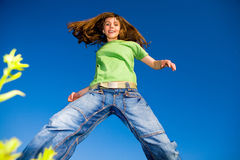 Happy young woman enjoying summer. Against the backdrop of blue sky Stock Images
