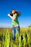 Happy young woman enjoying summer. Jumping. Against the backdrop of blue sky Royalty Free Stock Photos