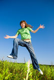 Happy young woman enjoying summer. Jumping. Against the backdrop of blue sky Stock Image