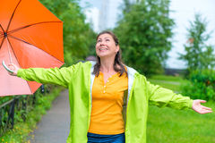 Happy young woman enjoying the summer rain. In the park royalty free stock image