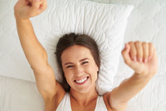 Happy young woman enjoying sunny morning on the bed royalty free stock image
