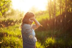 Happy young woman enjoying wonderful evening. Warm weather, summer, field Royalty Free Stock Image