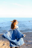Happy young woman enjoys sunny weather and posing on shore of bl Stock Photography