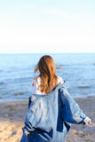 Happy young woman enjoys sunny weather and posing on shore of bl Royalty Free Stock Photo