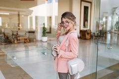 Happy young woman entering glass door into modern hotel, cafe, business centre. Wearing stylish glasses, pink jacket royalty free stock photos