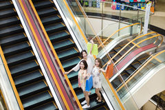 Happy young woman on escalator in shopping mall Stock Photo