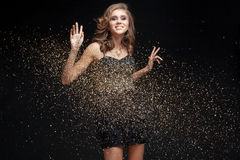 Happy young woman in an evening dress celebrating New Year. Or birthday on a black background with confetti Royalty Free Stock Photos