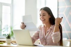 Happy young woman excited by reading good news in letter. Happy young woman student or employee excited by reading good news in paper letter about new job, great stock photo
