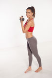 Happy young woman exercising with weights Royalty Free Stock Images