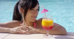 Happy young woman eyeing a large tropical cocktail stock video footage