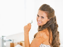 Happy young woman with eyelash curler in bathroom Royalty Free Stock Image