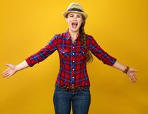 Happy young woman farmer on yellow background excited Royalty Free Stock Image