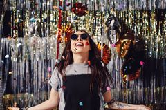 Portrait girl enjoying party and confetti. Happy young woman in fashionable clothes celebrating on a shimmer, colorful, party background. Party decorations gold royalty free stock photo