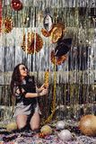 Portrait girl enjoying party and confetti. Happy young woman in fashionable clothes celebrating on a shimmer, colorful, party background. Party decorations gold royalty free stock images